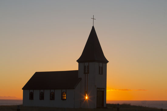 iceland chuch with sunstar at sunrise